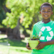 Boy in recycling tshirt holding potted plant — Stock Photo #46789097