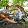 Man serenading his girlfriend on camping trip — Stock Photo #46789199
