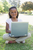 Girl sitting on grass using laptop — Foto Stock