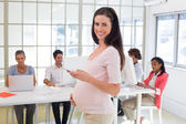 Pregnant office worker texts on phone — Stock Photo