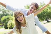 Couple spreading arms in the park — Stock Photo