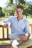 Man using tablet drinking coffee — Stock Photo