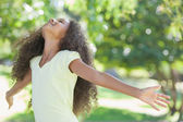 Girl smiling with arms outstretched — Stock Photo