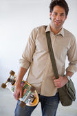 Businessman standing with his skateboard — Stock Photo