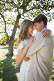 Young couple embracing in park — Stock Photo
