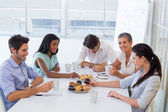 Work colleagues having hot beverages and muffins — Stock Photo