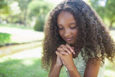 Young girl praying in the park — Foto de Stock