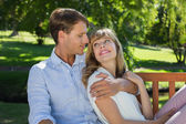 Couple relaxing on park bench — Stock Photo