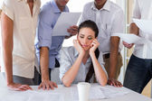 Worried businesswoman surrounded by colleagues — Stock Photo