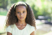 Girl frowning at the camera in the park — Stock Photo