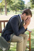 Worried businessman sitting on park bench — Stock Photo