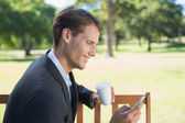 Businessman texting on phone on park bench — Stock Photo