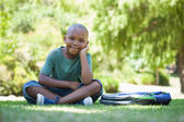 Happy schoolboy sitting on grass — Stock Photo