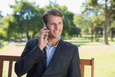 Businessman talking on phone on park bench — Stock Photo
