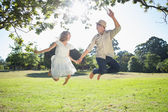 Cute couple jumping in the park — Stock Photo