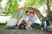Couple sitting in their tent showing affection — Stock Photo