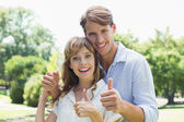 Couple showing thumbs up in the park — Foto de Stock