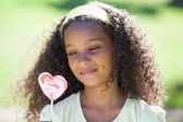 Girl holding a heart lollipop in the park — Stock Photo