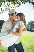 Blonde being lifted by boyfriend in the park — Stock Photo
