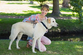 Blonde kneeling with her labrador in the park — Stock Photo