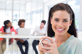 Businesswoman drinking coffee with coworkers — Stock Photo