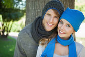 Cute couple smiling at camera in hats and scarves — Stock Photo