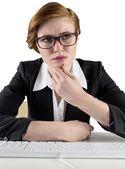 Thinking businesswoman sitting at keyboard — Stock Photo