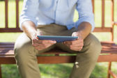 Man on park bench using tablet — Stock Photo