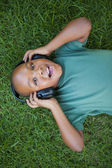 Boy lying on grass listening to music — Foto de Stock