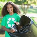 Постер, плакат: Environmental activist picking up trash