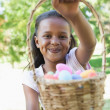 Girl showing basket of easter eggs — Stock Photo #46791637