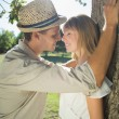 Couple leaning against tree in the park — Stock Photo