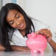 Businesswoman putting coins into piggy bank — Stock Photo #46794183