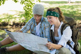Couple on a hike reading map — Stock Photo