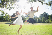 Couple jumping in the park — Stock Photo