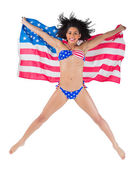 American girl leaping holding flag — Stock Photo