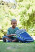 Schoolboy opening his schoolbag — Stock Photo