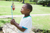 Boy blowing pinwheel in the park — Stock Photo