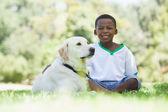 Chłopiec siedzi z jego labrador w parku dla zwierząt domowych — Zdjęcie stockowe