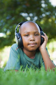 Boy lying on grass listening to music — Foto Stock