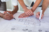 Architects drawing on the blueprints — Stock Photo