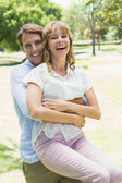 Man picking up his girlfriend in the park — Stock Photo
