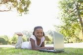 Chica acostada en césped usando laptop — Foto de Stock