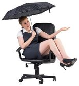 Businesswoman holding umbrella sitting on chair — Stock Photo
