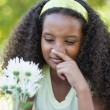 Girl holding a flower and covering her nose — Stock Photo #48234557