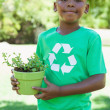 Boy in recycling tshirt holding potted plant — Stock Photo #48234635