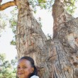 Girl sitting by large tree — Stock Photo #48234721