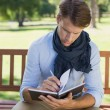 Man writing in his notepad on bench — Stock Photo