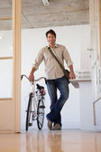 Businessman standing with his bike — Stock Photo