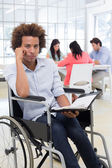 Businessman in wheelchair holds planner — Stock Photo